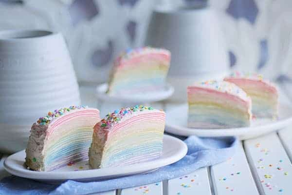 5 slices of crepe cake in rainbow colors laid out on a table with sprinkles scattered around.
