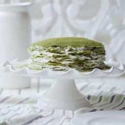 Side profile of a matcha crepe cake on a cake stand.