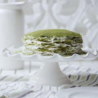 Side profile of a matcha crepe cake on a cake stand.