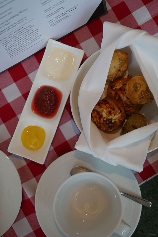 Variety of scones wrapped in a napkin set on top of a plate.