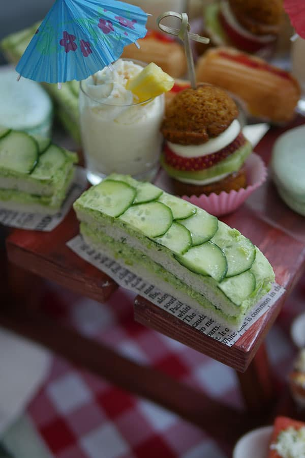 Cucumber sandwiches laid on top of a mini picnic table tea display.