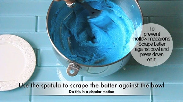 Macaron batter is being mixed with a spatula during the macaronage stage of making macarons.