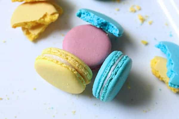A variety of macarons in different colors laid out onto a plate.