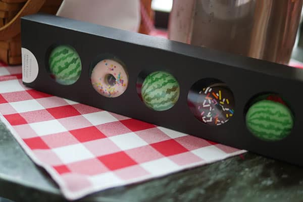 Fancy macarons and cookies in the shape of watermelons and donuts set inside a gift box.