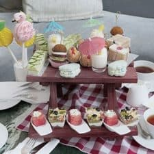 Afternoon tea treats displayed on a picnic bench.