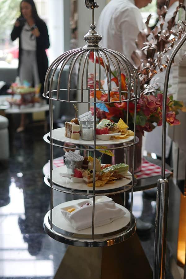 Afternoon tea set laid inside a birdcage.