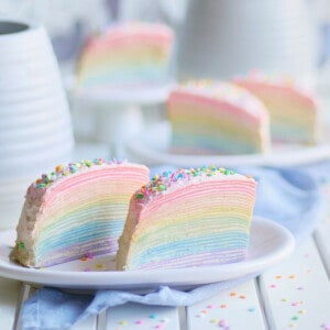 Rainbow Crepe Cake on a small plate with some slices in the back.