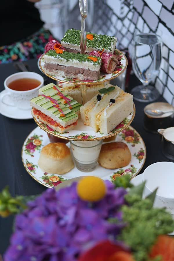 A full 3-tier high tea tray filled with finger sandwiches and scones.