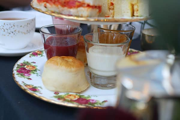 The lowest tier on the 3-tier cake stand is holding scones and condiments.