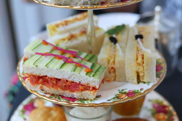 Side profile of finger sandwiches on a tea tray.