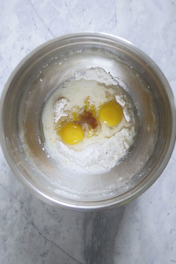 Egg yolk, vanilla, salt, flour, milk inside a stainless steel mixing bowl.