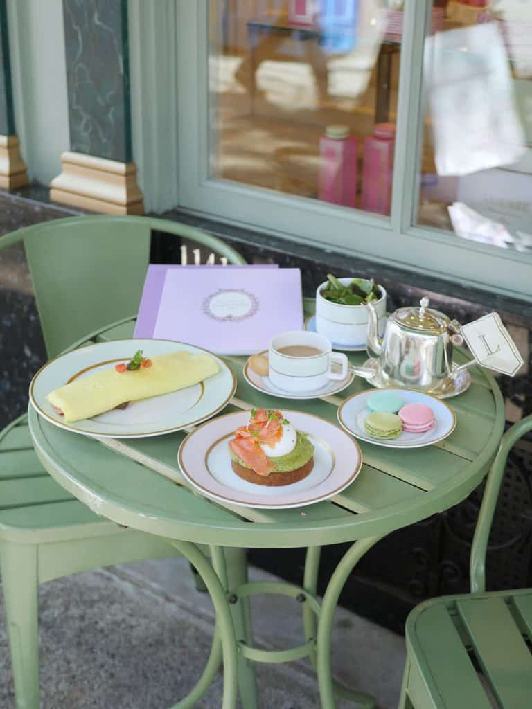 Brunch food on a green picnic table at Laduree Canada's patio.