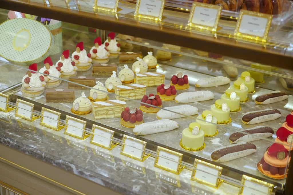 New laduree desserts lined up in display case.