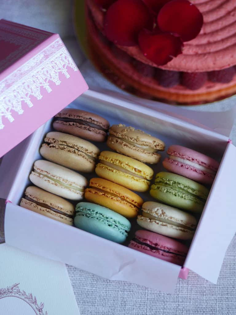 A box of 12 Laduree macarons with a big macaron cake in the back.