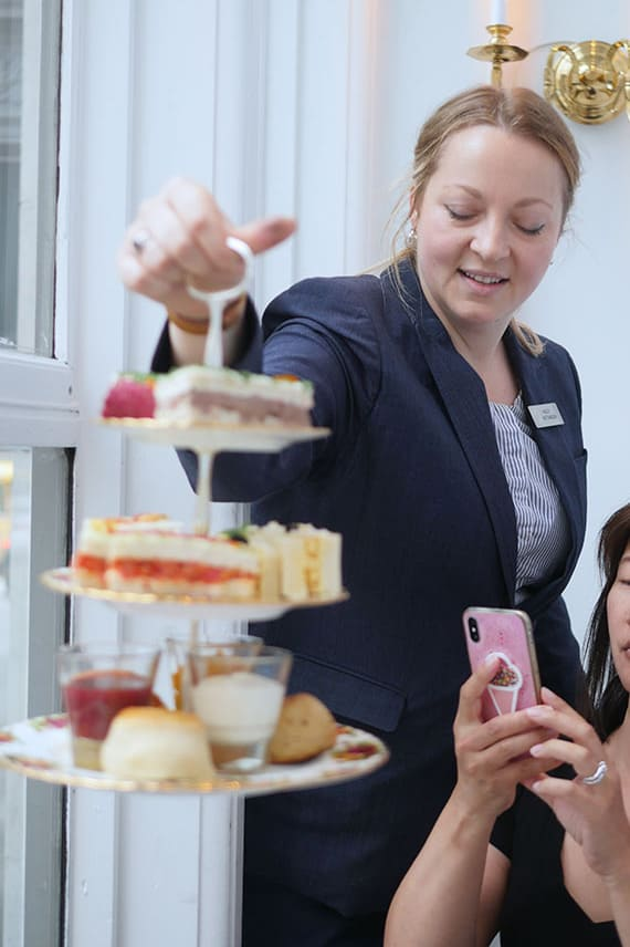 A server drops off a 3-tier tea stand full of finger sandwiches and scones.