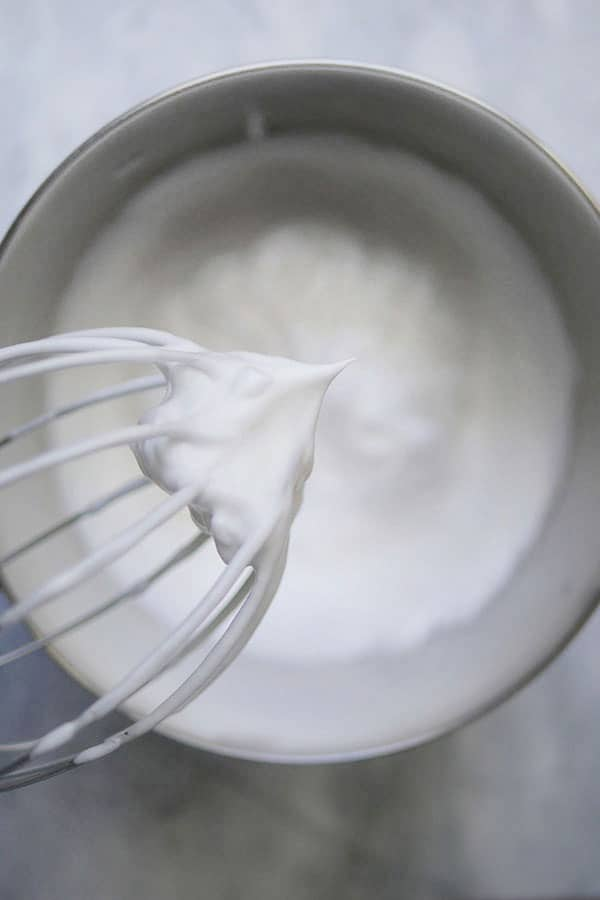 Meringue clumped inside a whisk in the stiff peak stage.