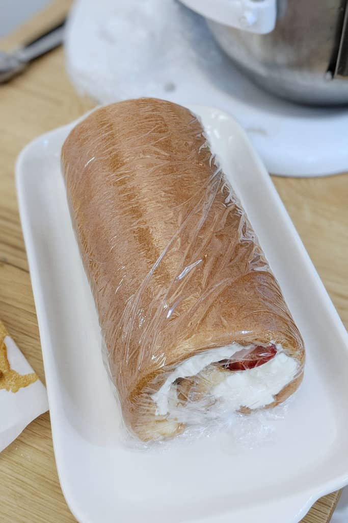 Cake rolled up with plastic wrap on a dish.