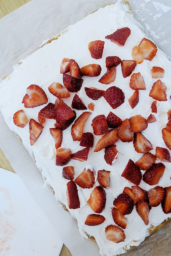 Cut up strawberries spread out evenly on a bed of cream on an unrolled cake roll.