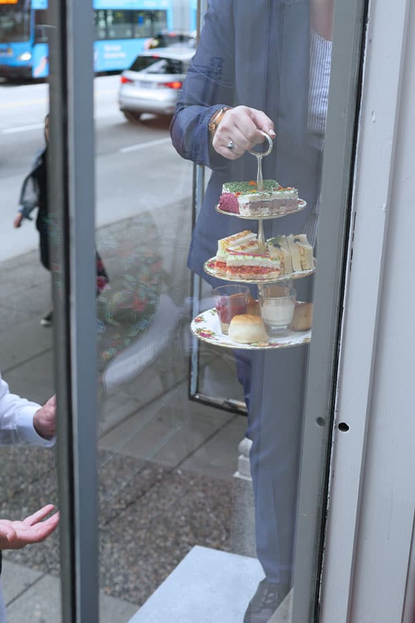 Afternoon tea on a 3-tier tea tray being brought up to the diners in the display window.