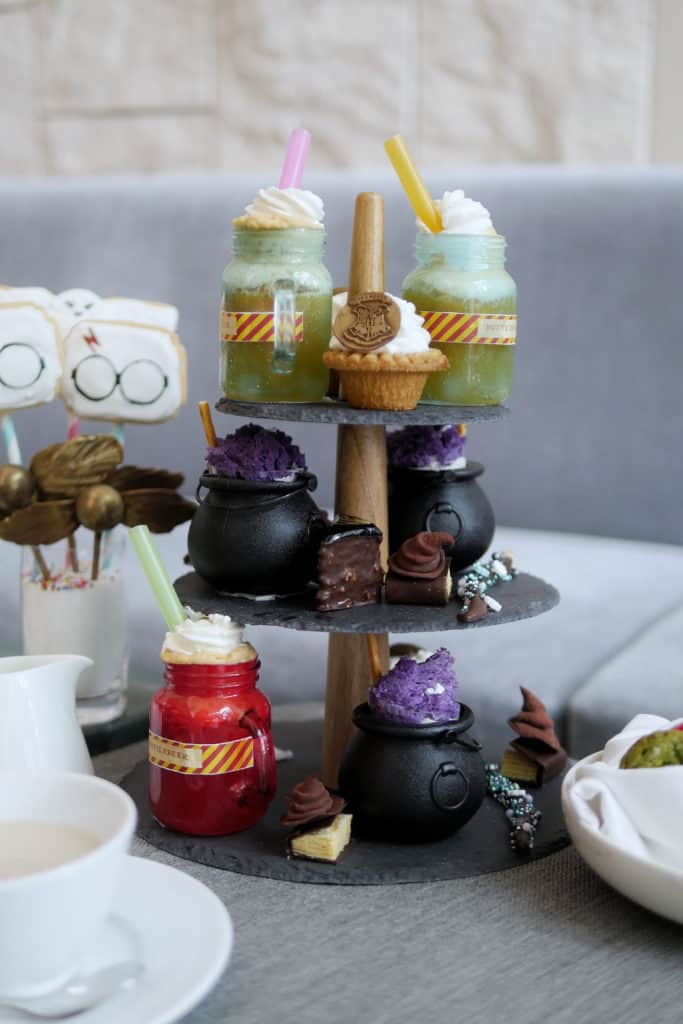 Mini butter beer and witches cauldron treats on a 3-tier tea tray.