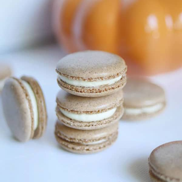 Pumpkin spice cheesecake macarons stacked in front of a pumpkin.