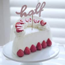 "A half birthday cake made from whipped cream and fresh strawberries topped with a cake topper that says ""half""."