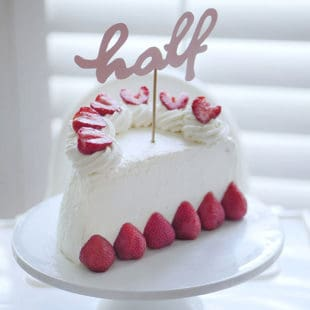 """A half birthday cake made from whipped cream and fresh strawberries topped with a cake topper that says """"half""""."""