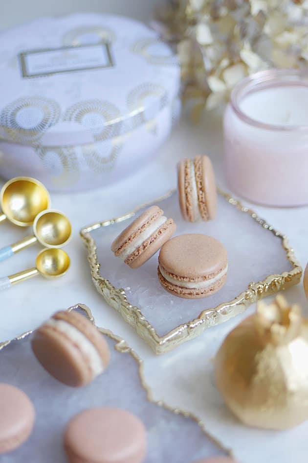 A bunch of gingerbread spice macarons amongst a variety of kitchen utensils and plates with gold trim.