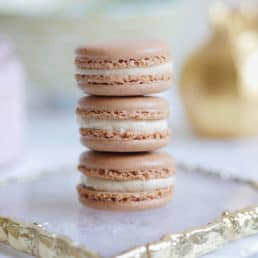 A stack of 3 gingerbread spice macarons on an agate plate.