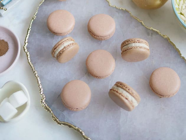Bird's eye view of many gingerbread macarons on an agate plate trimmed with gold. Plates of of spice and sugar flank the sides.