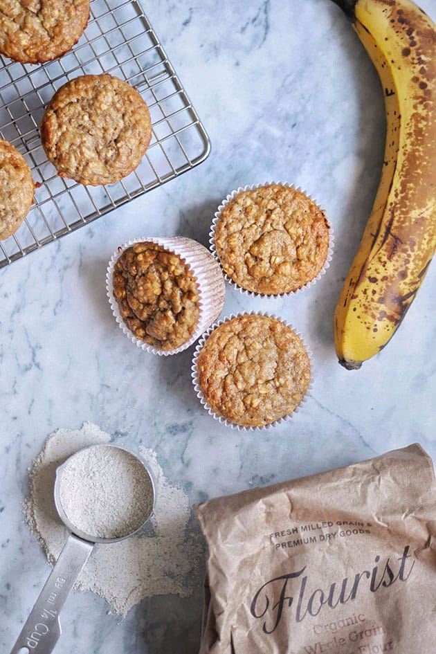 Banana oat muffins on marble counter with Einkorn flour bag and measuring cup.