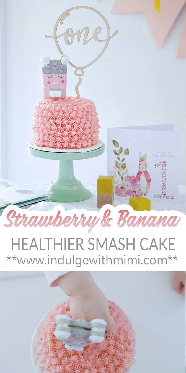 A pink smash cake for baby with macaron topper and one cake topper on a green cake stand.