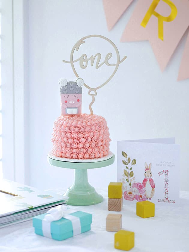 A mini pink smash cake on a green cake stand placed on a table with kid's wooden blocks and a birthday card.
