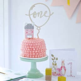 A decorated smash cake on a cake stand with a birthday card on the side.