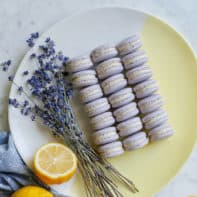 purple macarons on a dish with lavender and lemons