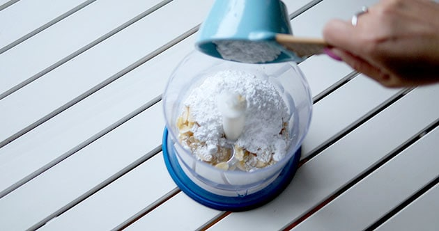 Pouring powdered sugar into a food processor.
