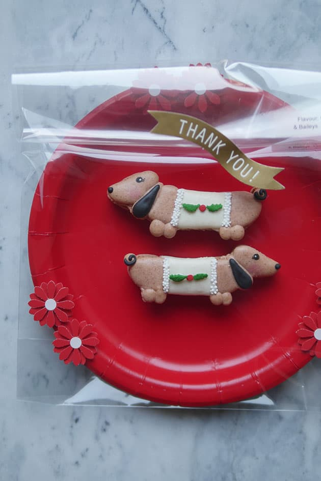 Wiener dog macarons on a red paper plate.