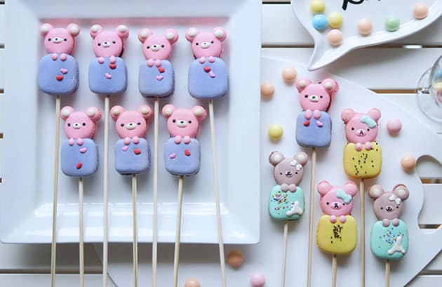 A variety of bear shaped macarons styled against a white plate.