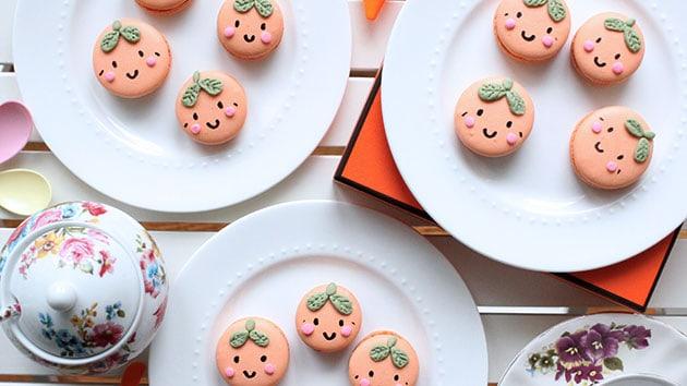 Mandarin orange macarons on 3 plates.