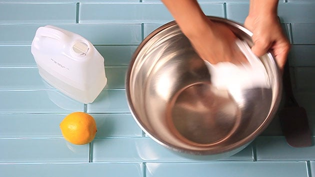 Wiping down a stainless steel bowl with lemon juice.