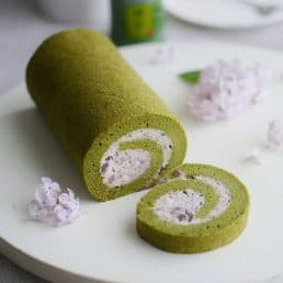 Matcha green tea cake roll with a slice cut out showing the red bean cream inside.