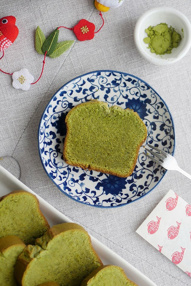 A piece of matcha pound cake on a small dessert plate with japanese motif.