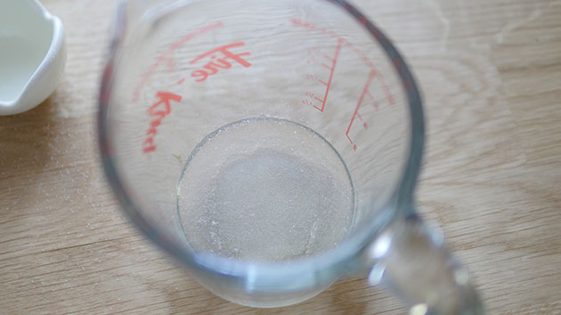 Close up of measuring cup with bloomed gelatin in a solid form.