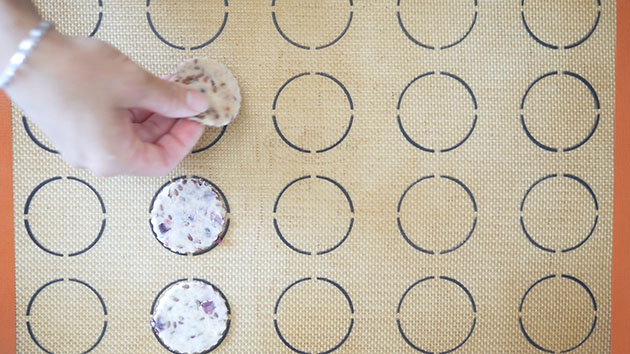 Hand placing crackers on baking mat.