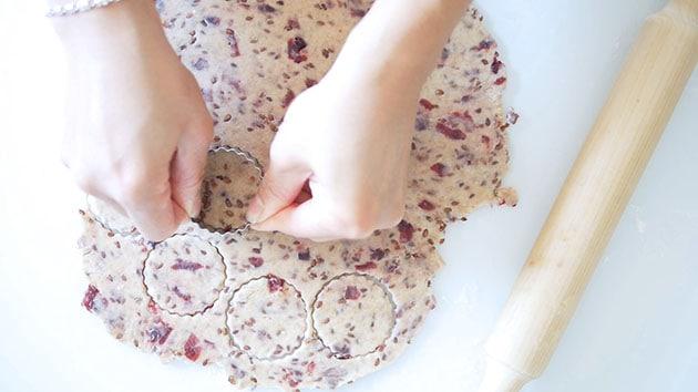 Pressing cookie cutter into cranberry sourdough cracker dough.