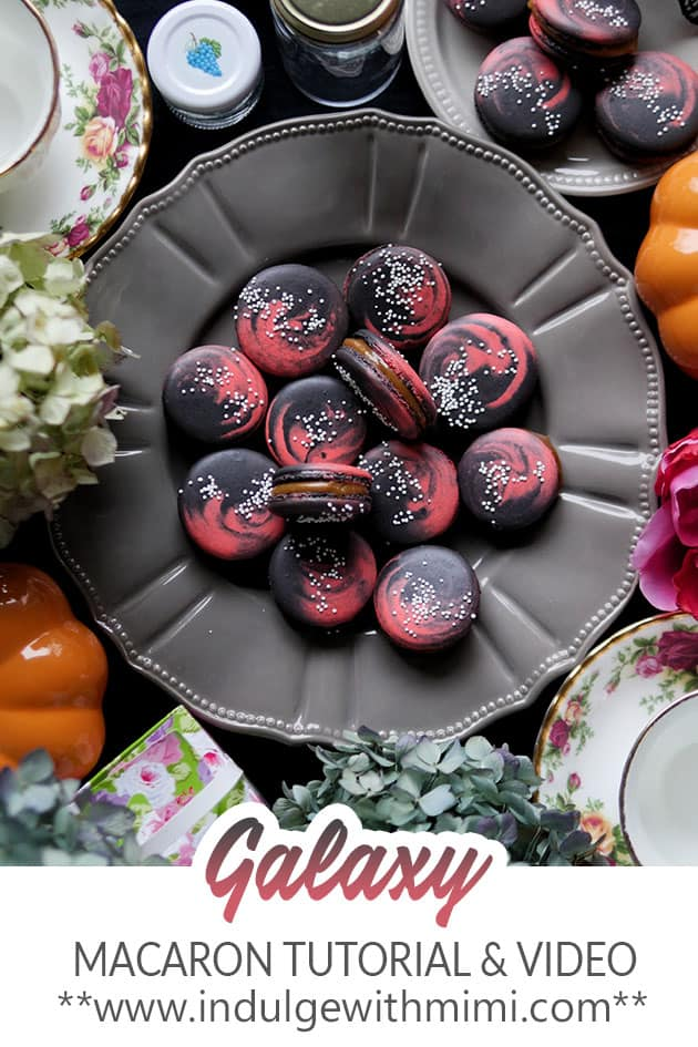 Galaxy macarons on a grey decorative plate.