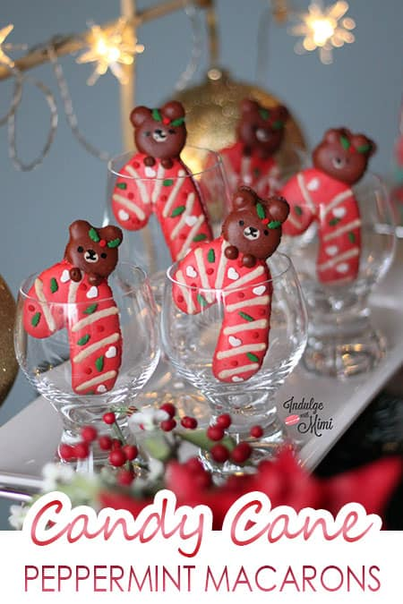 Christmas bears hanging onto a candycane macaron.