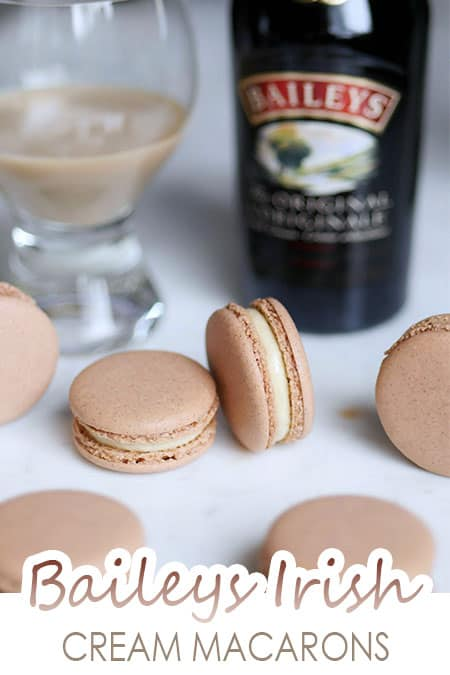Baileys irish cream macarons with Baileys liqueur bottle in the back.