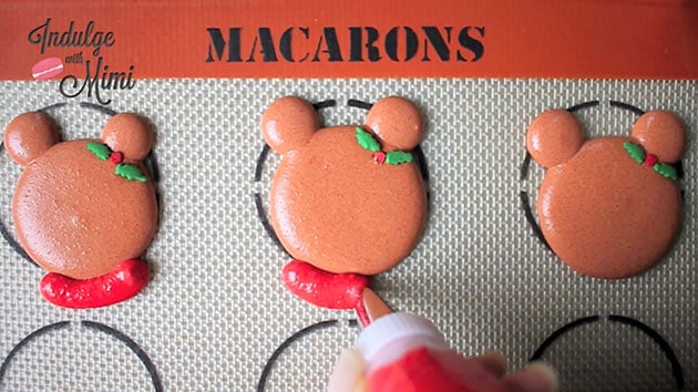 Ugly sweater being piped onto bear macaron head.