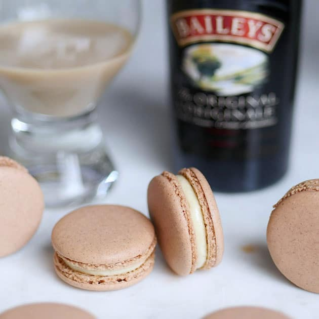 Gingerbread Baileys Irish Cream macarons on a table with a bottle of Baileys in the back.